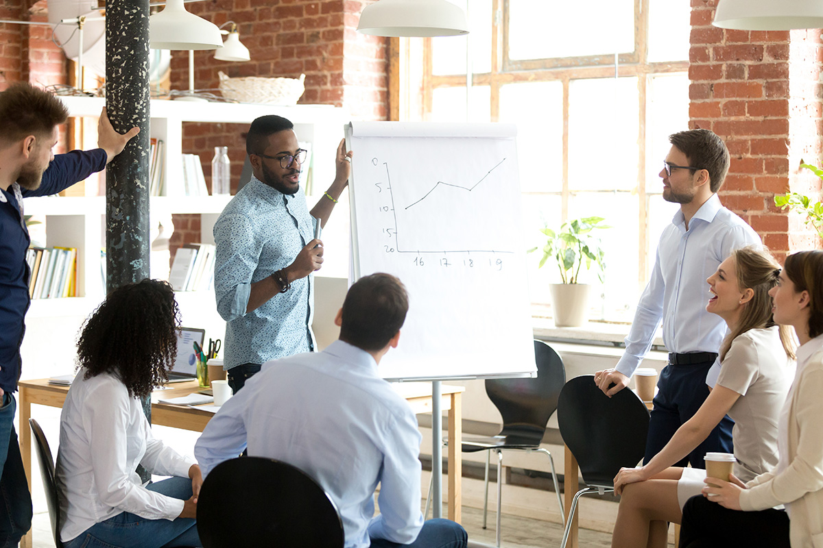 Confident smiling African American business coach speaking presentation to colleagues group at briefing, company meeting, explaining growth of sales graph, reporting about good result, motivating workers