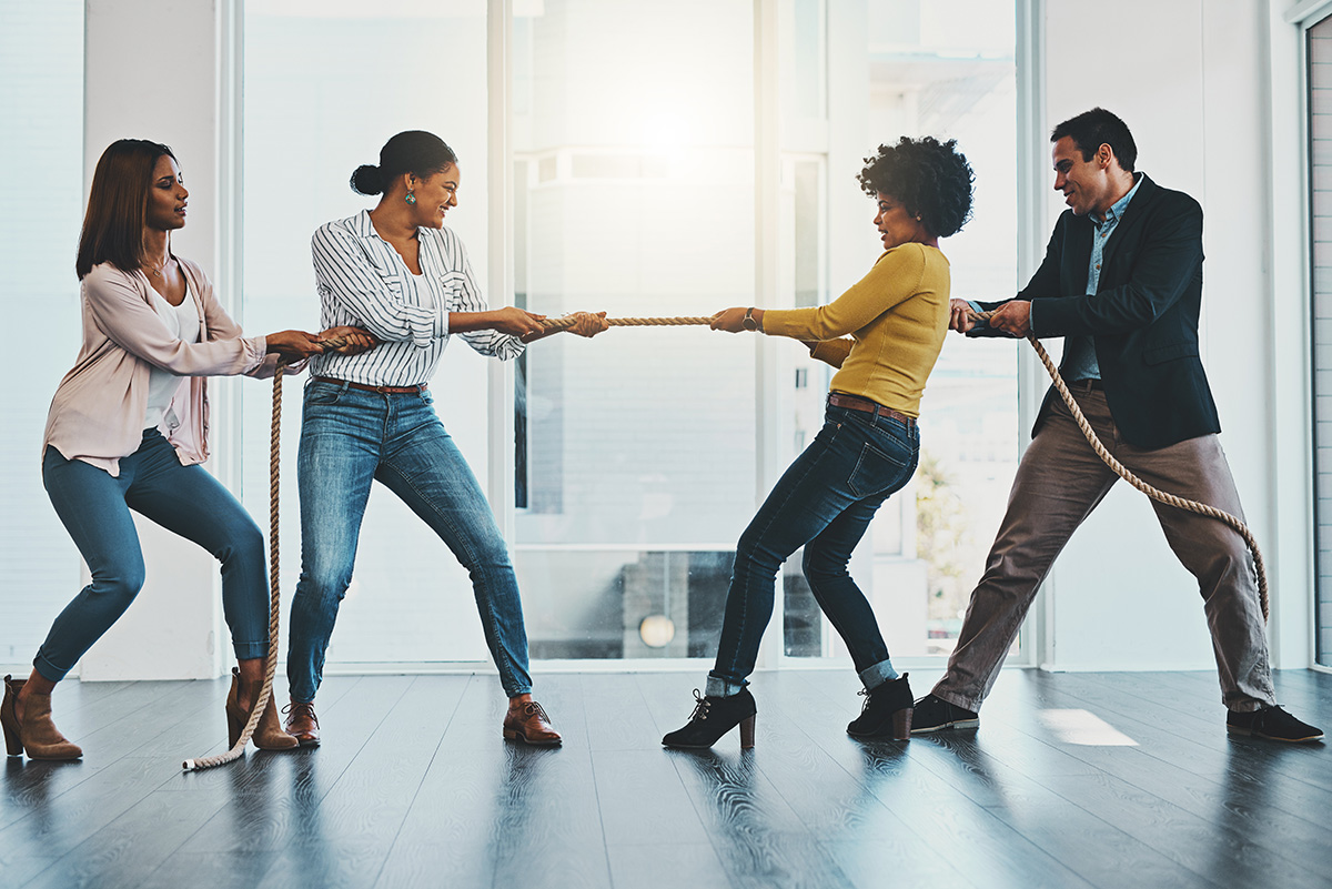 Shot of a group of businesspeople pulling on a rope during tug of war in an office