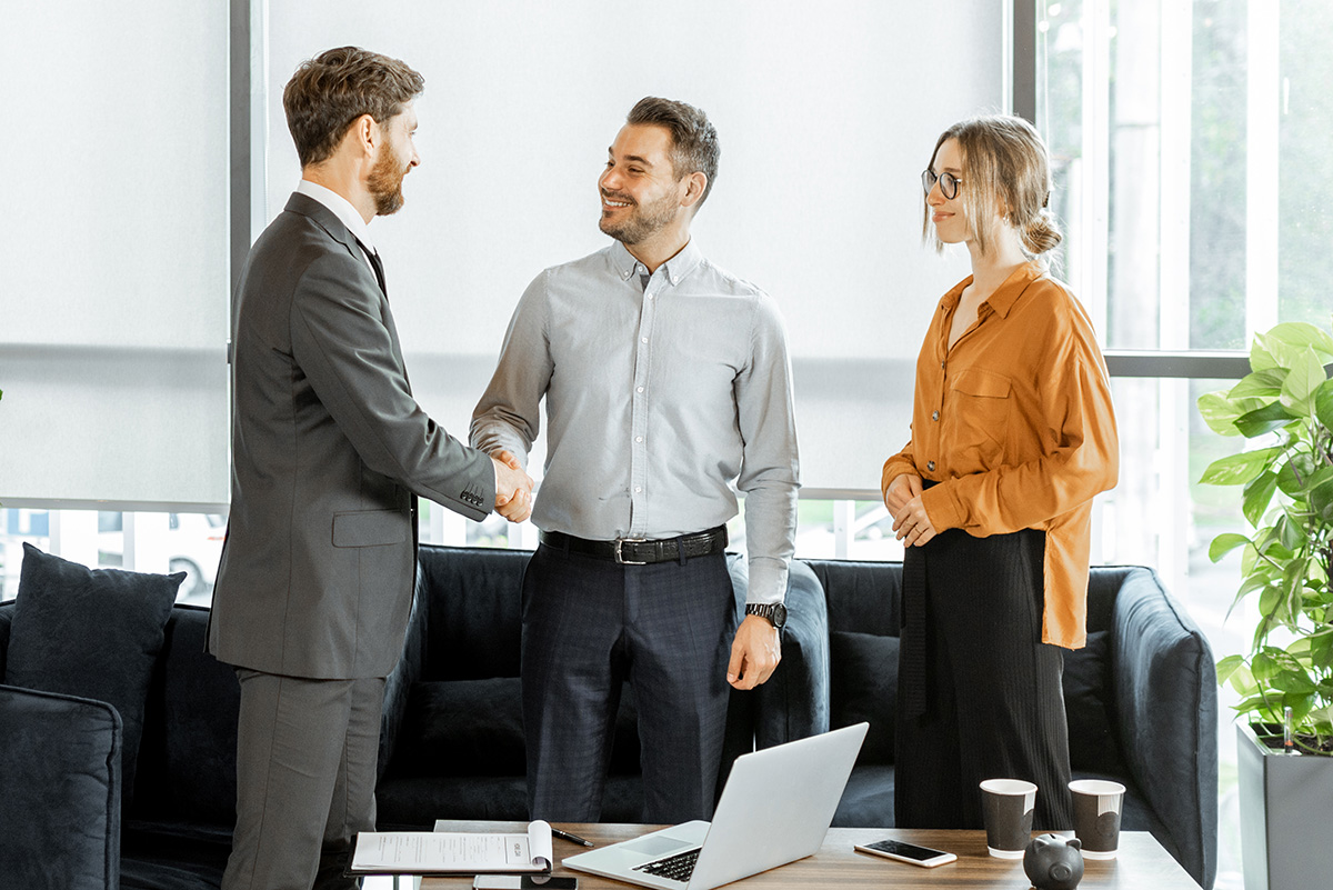 Young and happy couple having a deal, shaking hands with financial consultant or real estate agent at the luxury office